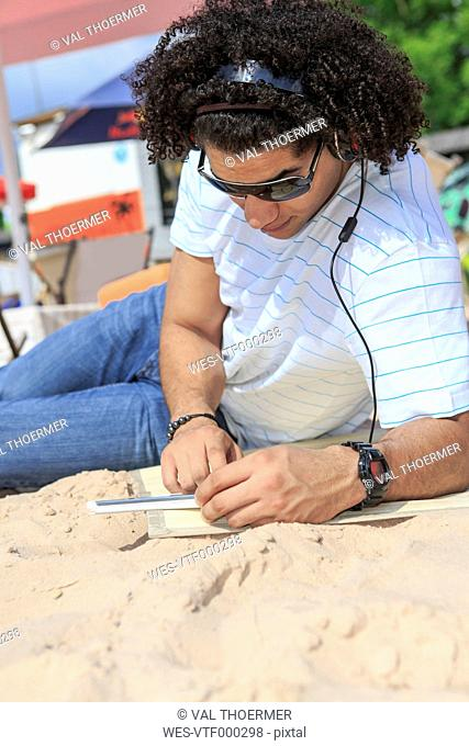 Young man with digital tablet listening music on the beach