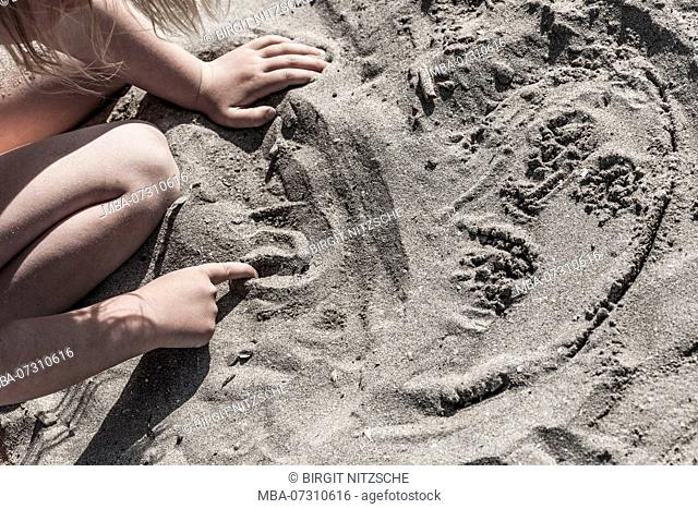 Child paints in the sand