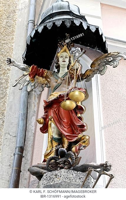 Angel with golden scales in her hand standing on the head of a devil, baroque house statue, Judengasse lane, old town, Salzburg, Austria, Europe