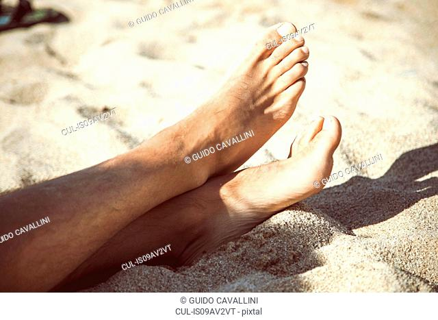 Cropped view of bare feet on sandy beach, Costa Paradiso, Sardinia, Italy