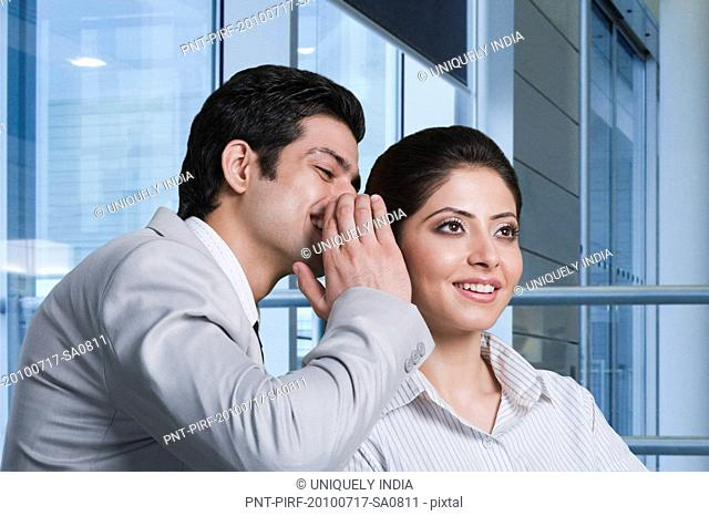 Businessman whispering to a businesswoman