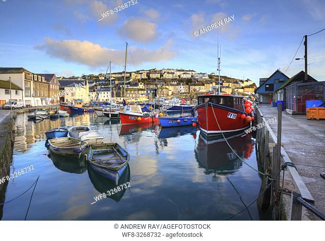 Boats in the inner harbour at Mevagissey on the south coast of Cornwall, captured shortly after sunrise on a still morning in late January