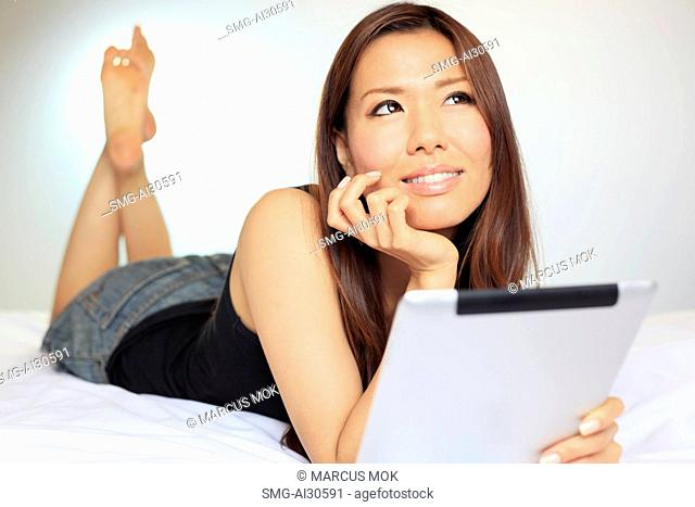 Young woman laying on her stomach using a digital tablet