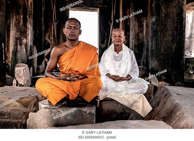 Senior and young monk meditating in temple in Angkor Wat, Siem Reap, Cambodia