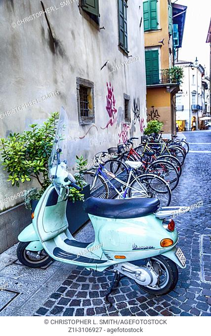 Powder blue vespa parked beside a row of bicycles in a street in Udine, Italy