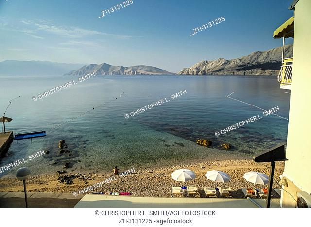 Silence and stillness at daybreak at the waters edge of the adriatic at Baska on the Croatian island of Krk
