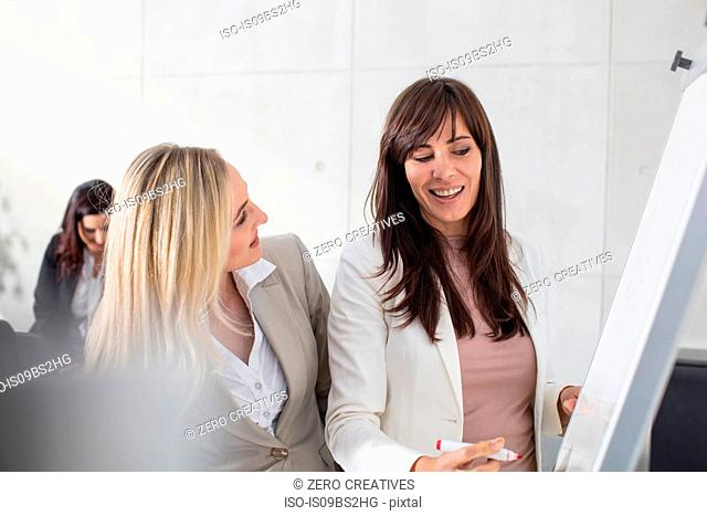 Businesswomen talking to colleague and writing on whiteboard in office
