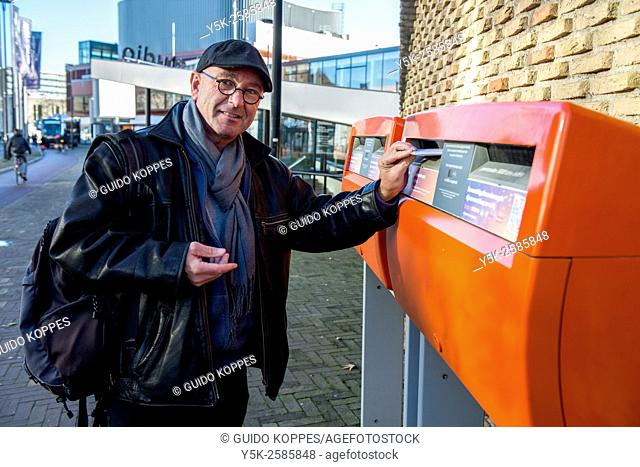 Tilburg, Netherlands. Man with cap and glasses posting an enveloppe in a Dutch mailbox