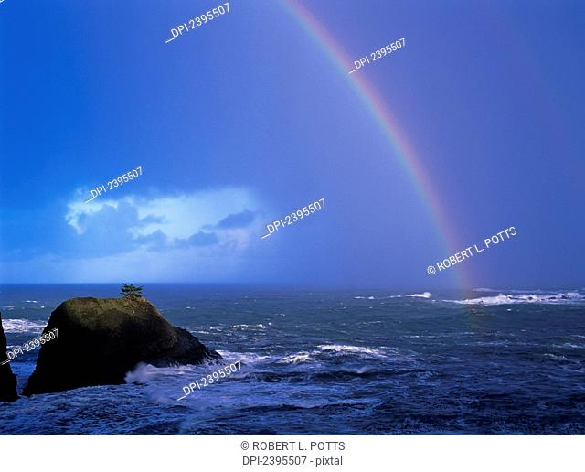 A rainbow brightens the sky over the ocean; Charleston, Oregon, United States of America