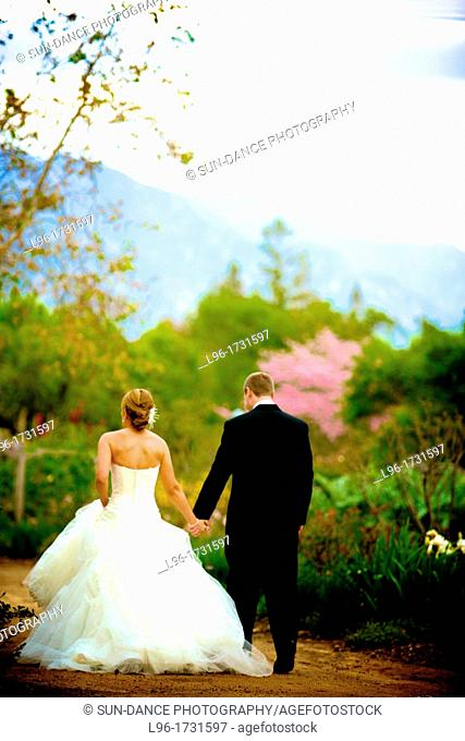 hand in hand, this happy married couple heads to their romantic garden reception to celebrate