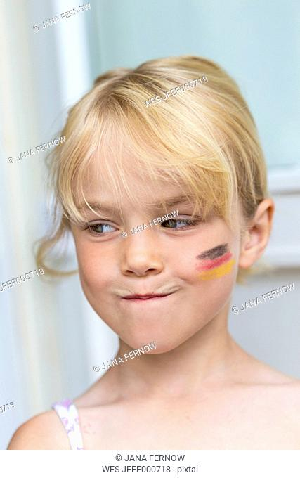 Portrait of blond little girl with German Flag painted on her cheek