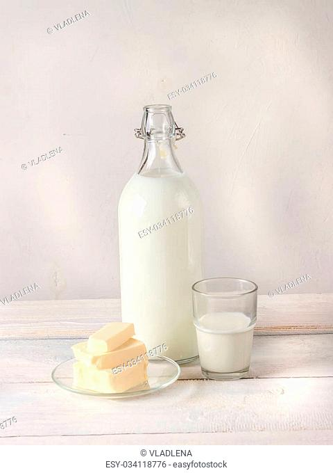 Dairy products: bottle of milk, butter and glass of milk on white wooden background. Style rustic. Selective focus