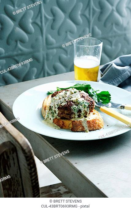 Plate of burger with herb sauce
