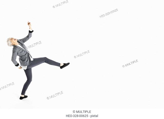 Playful, energetic senior woman dancing against white background