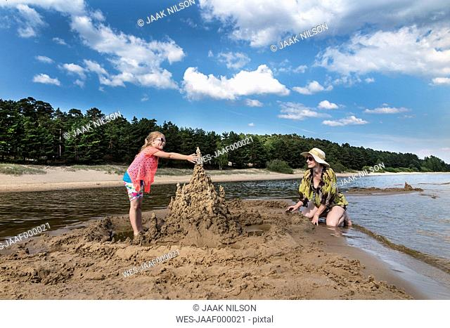 Estonia, Lake Peipus, Kauksi beach, girl and mother building sandcastle