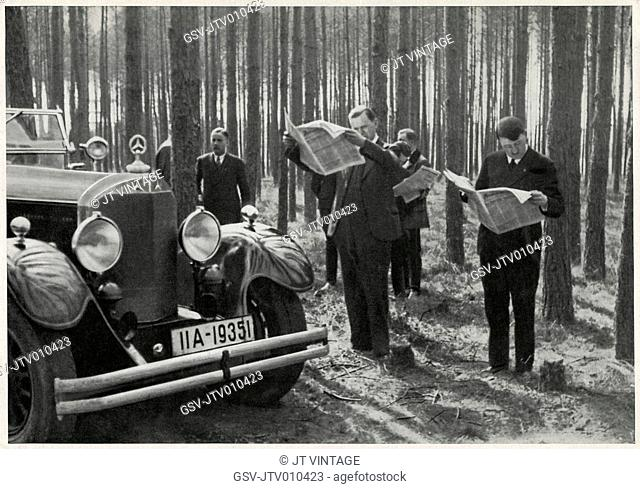 Adolf Hitler and Entourage Standing Alongside his Mercedes while Reading Newspapers in the Woods, Germany, early 1930's
