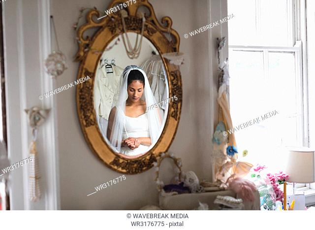 Reflection of young bride in a wedding dress in the mirror