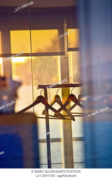 Hangers on clothing rack. Through the window there is a blurred landscape at sunset