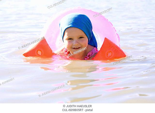 Portrait of female toddler wearing rubber ring and inflatable armbands in Lake Seeoner See, Bavaria, Germany