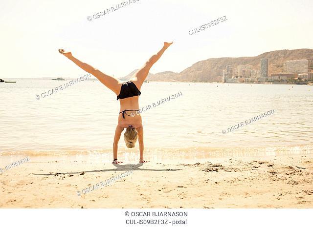 Rear view of woman in bikini cartwheeling on beach, Alicante, Spain