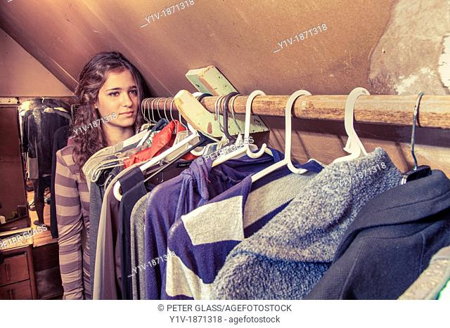 Teen girl in her mother's clothes closet