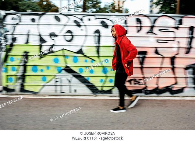Young man wearing red hoodie passing a graffiti wall