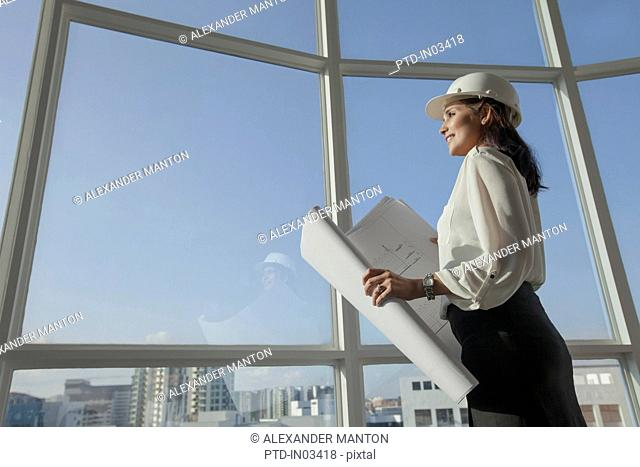 Singapore, Female architect with hardhat and building plans looking through window