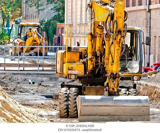Big excavators at urban construction site