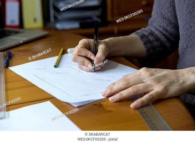 Close-up of woman drafting ground plan at desk