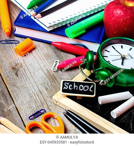 Still life, business, education concept. Assortment of office and school supplies, alarm clock and chalkboard on a rustic wooden table