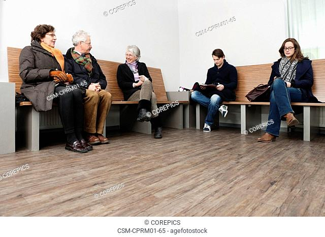 Several people from all ages sitting in a crowded hospital waiting area