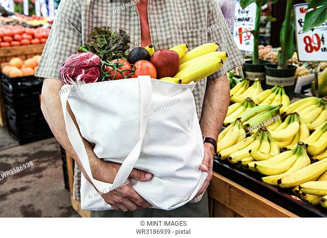 Close up of person at a food and vegetable market, holding shopping bag with fresh produce including bananas, tomatoes and cabbage