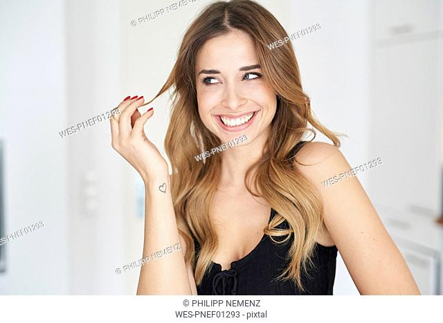 Happy young woman wearing black dress playing with her hair