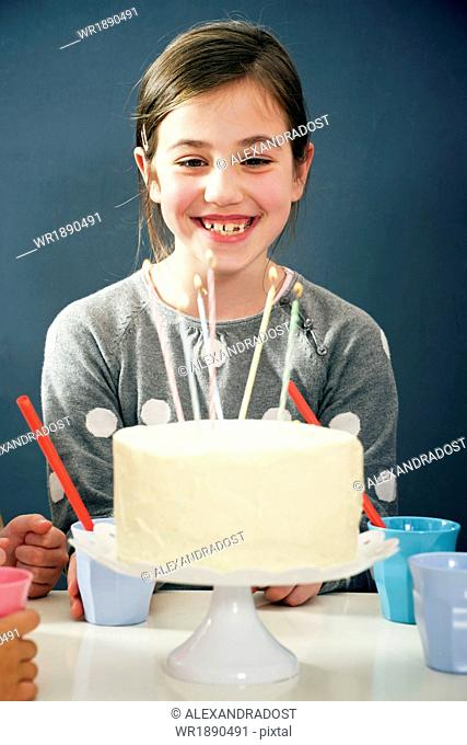 Girl on birthday party looking at candles on cake, Munich, Bavaria, Germany