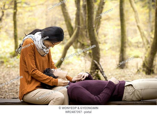 Side view of young romantic couple having a date on bench in forest face to face