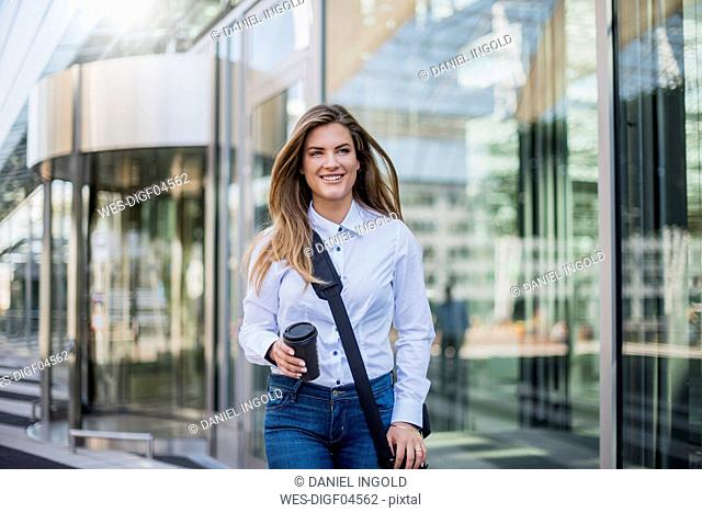 Smiling young businesswoman with bag and coffee to go