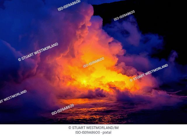 Smoke clouds from lava flow impacting sea at dusk, Kilauea volcano, Hawaii