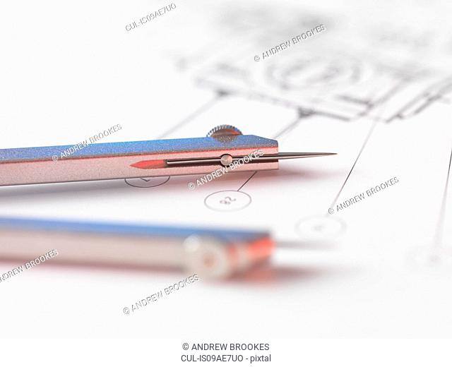 Dividers sitting on engineering drawing used in the measurement of design features