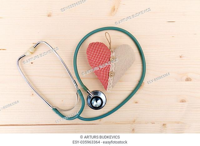 Stethoscope and red fabric heart lying on wooden table. Healthcare, cardiology and medical concept