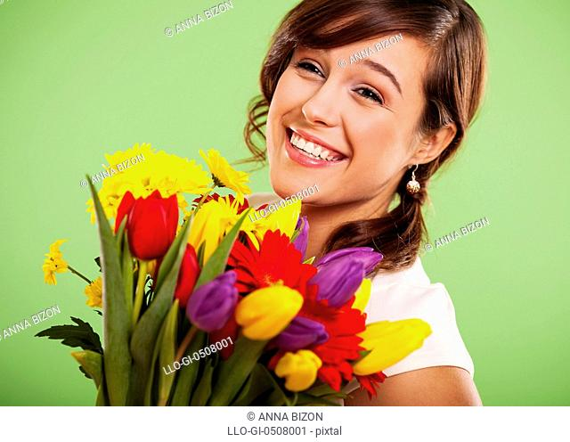 Portrait of a smiling woman with colorful flowers, Debica, Poland Debica, Poland