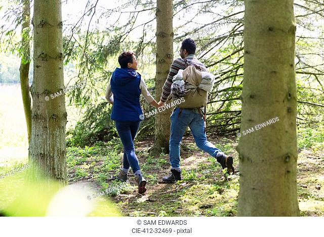 Couple holding hands and hiking with backpack in woods