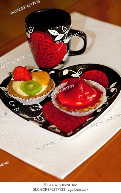 High angle view of assorted tarts with a cup of coffee