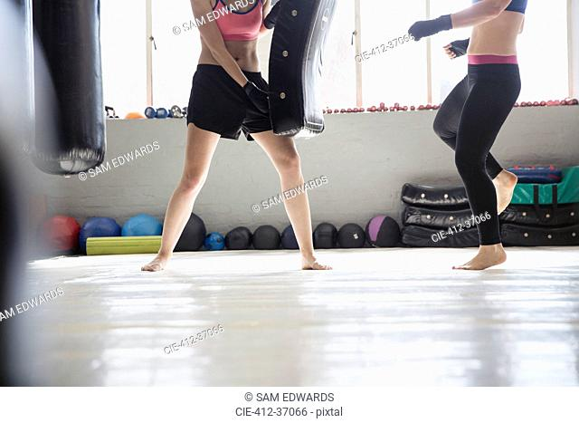 Young women shadowboxing with padding in gym