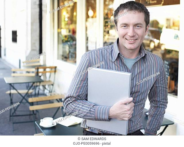 Man on outdoor patio holding laptop