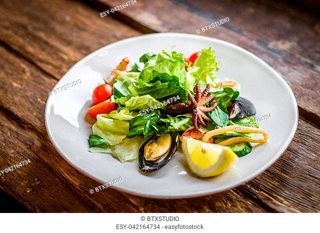 Tasty salad with seafood on a white plate