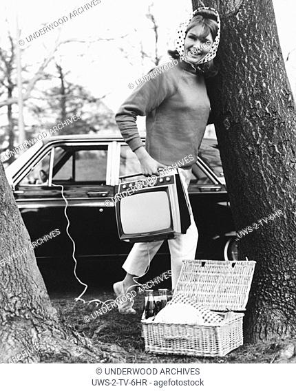 Batavia, New York: 1965.A young woman gets ready for a picnic with her Sylvania GT-12 fully transitorized 12 inch black and white television set that is plugged...