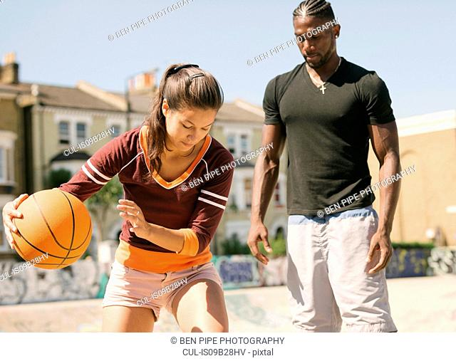 Woman and young man practising basketball in skatepark