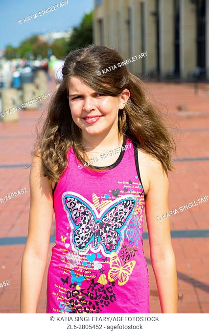 Gorgeous long hair caucasian preteen in her 10, 11, 12, 13 years old walking on the boardwalk. She is wearing a butterfly teeshirt pink and she is smiling...