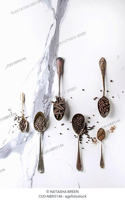 Variety of different black peppers allspice, pimento, long pepper, monks pepper, peppercorns and ground powder in vintage spoons over white marble texture...