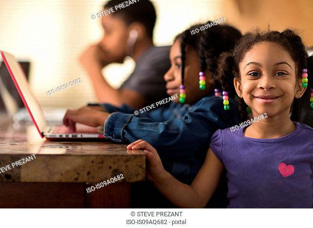 Portrait of girl at dining table and siblings using laptops